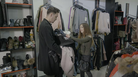 Upset disappointed fiancee puts the clothes back to their place in a boutique Footage