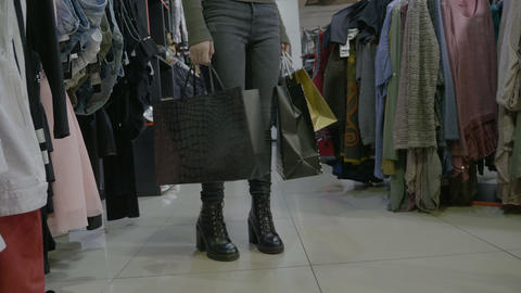 Beautiful college girl walking in high heels holding shopping bags in a clothing Footage