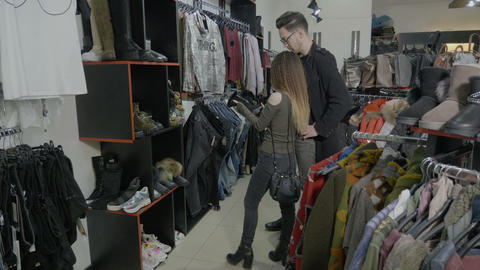 Young student couple walking in a clothes store mall looking for the right pair Footage