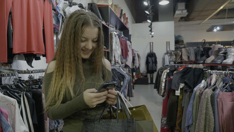 Beautiful social media influencer doing her shopping receives messages and Footage