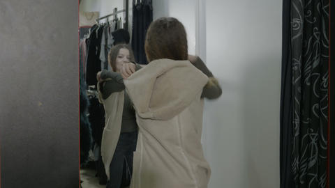 Beautiful popular woman shopping trying clothes in the fitting room and looking Footage