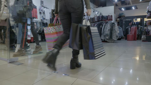 Spoiled attractive teenager girl holding shopping bags and walking in heels in a Footage