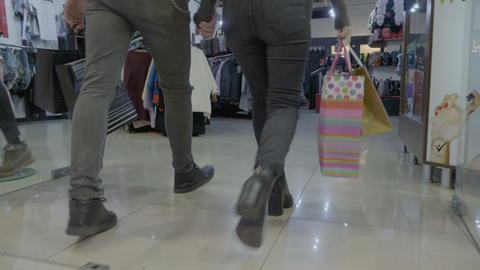 Attractive fashionable couple holding hands and shopping bags walking together Footage
