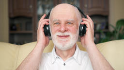 Modern senior man listening music with wireless headphones. Pensioner meloman Footage