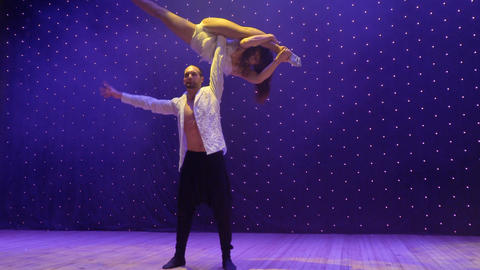 Acrobats performs tricks during young couple sing song, stage of theatre ビデオ