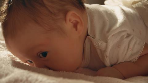 Baby girl trying to crawl on the bed Photo