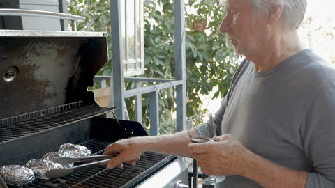 Handsome elderly senior man in his 70s holding a glass of red wine grilling Image