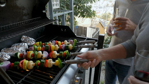 Tilt up from a bbq grill with vegetables to two men age 40 and 70 cooking ビデオ