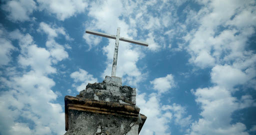 Time lapse of the clouds moving by an old cross against a blue sky Image