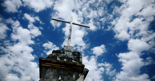 Time lapse of the clouds moving by an old cross against a blue sky - color Footage