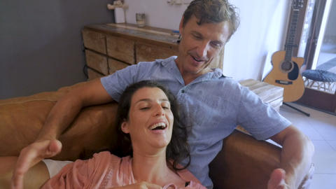 Beautiful couple in love looking at one another while using a digital tablet in Footage