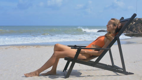 Blond Girl Relaxes in Beach Wooden Chaise Longue Live Action