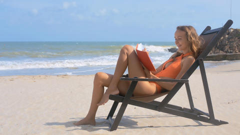 Girl Reads in Chair on Tranquil Ocean Beach Smiles Stock Video Footage