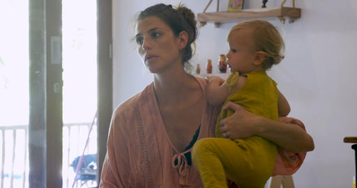 Young attractive stay at home mother holding a toddler baby talking to someone Footage