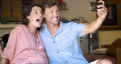 Pregnant woman and man taking selfies with a mobile smart phone making silly Image