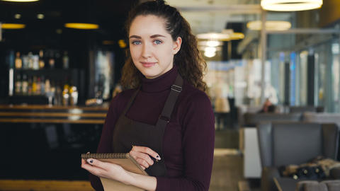 Portrait of cheerful and beautiful young waitress standing, keeping menu, and Footage