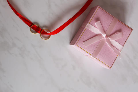 Pink gift box and wedding rings tied with ribbon Photo