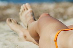 Young woman legs sunbathing on the beach Photo