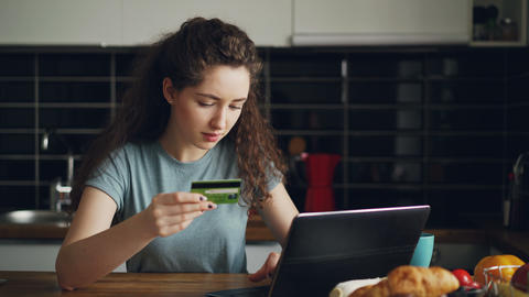 Cheerful young woman having online shopping using laptop computer and credit Footage