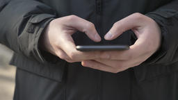 Male hands typing on a larger black smartphone outdoor. Texting message concept Footage