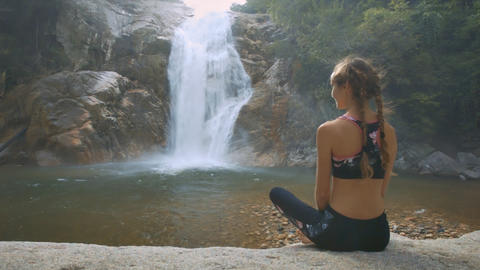 Woman Sits on Stone Takes Pleasure in Waterfall View Footage