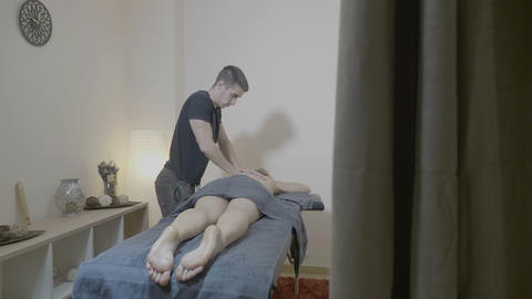 Attractive blonde woman enjoying professional back massage using elbow movements Footage