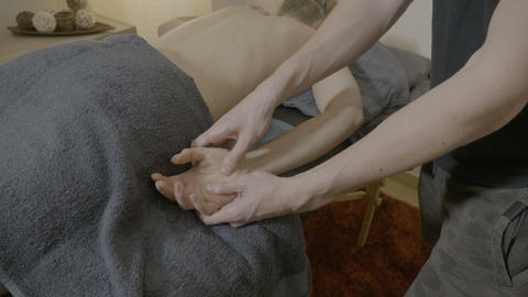Male therapist massaging the hand and wrist of a young beautiful blonde client Live Action