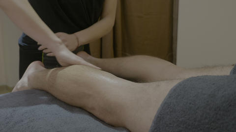 Beautiful female spa employee giving an intense therapeutic massage to young man Footage