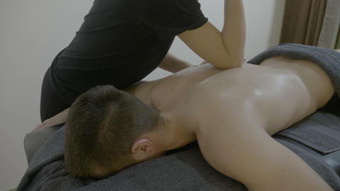 Famous man entrepreneur getting a thai oily massage from a female chiropractor Footage