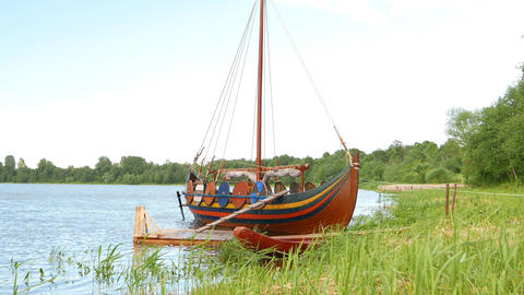 Wooden Karve boat stand at green grass river shore, rural area Footage