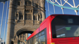 Camera tilts down from the south Tower of Tower Bridge to a London Bus passing u Footage