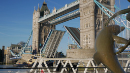 Tug boat passes under Tower Bridge on a sunny autumn morning. Framed by the stat Footage