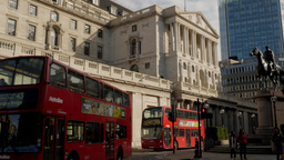 Wide shot of the Bank of England in London as two red double deckers buses drive Footage