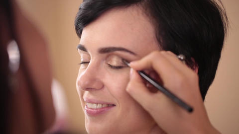 A make-up artist paints a girl's eyelid. Close-up Footage