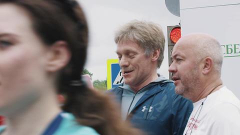 Russian politician Dmitry Peskov smiling talking at finish line of marathon Footage