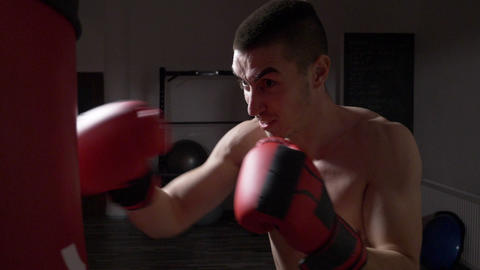 Professional coach boxer offering punching lessons in a dark gym in slow motion Footage
