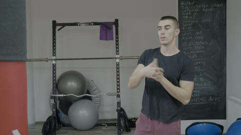 Young attractive male boxer warming up his arms before starting the training in Footage