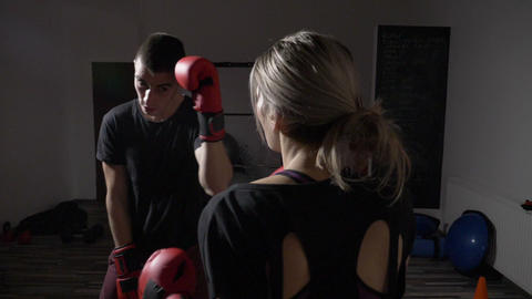Beautiful fit female kickboxer training hard for the big match with her male box Footage