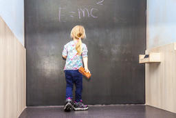 Cute little girl writing on chalkboard フォト