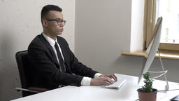 Young successful businessman in glasses works on the computer in the office Footage