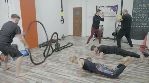 Athletic young men and a woman working out together at high intensity in a small Footage