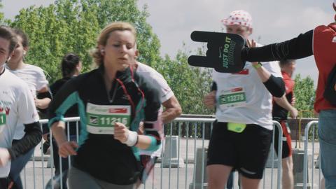 Cheering fan holding foam arm toward marathon running sportsmen Footage
