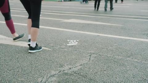 Legs of people walking on wet asphalt with road marking Footage
