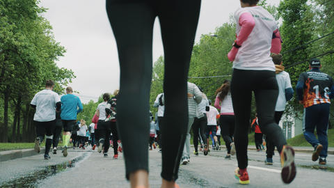 Legs in leggings of woman running marthon with athletes crowd Live Action