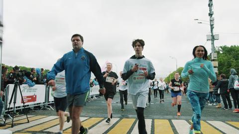 Crowd of sportive athletes running towards camera during marathon Footage