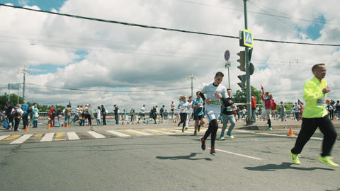 Sportive athletes running marathon around metal fencing at city crossroad Footage