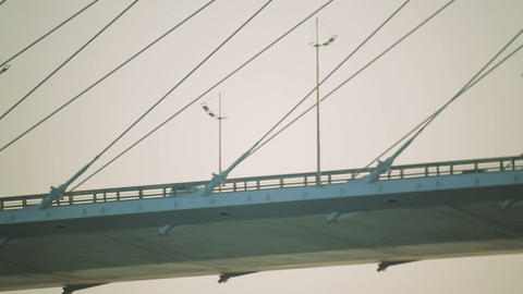 Cars drive to the bridge. Pylons of the bridge on the background of sunset sky Footage