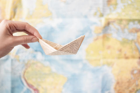 paper boat made of old printed paper on world map background . Travel sea Photo