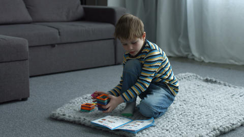 Little boy playing with magnetic constructor toy Footage