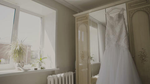 Fluffy wedding dress on a hanger in hotel room. Wedding morning Live Action